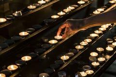 Candele e la mano che mette una nuova candela Fotografie Stock Libere da Diritti