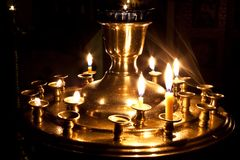 Candele e una lampada che brucia nella chiesa. Fotografia Stock