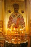 Candele ed icona in chiesa russa Fotografie Stock