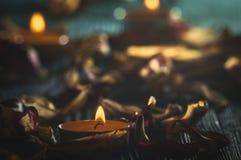 Candele gialle e plamennoi circondati dai petali asciutti dei tulipani Immagine Stock Libera da Diritti