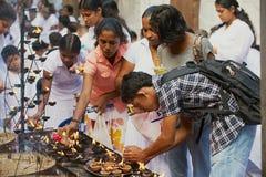 Candele leggere della gente al tempio buddista durante la celebrazione religiosa di Vesak a Colombo, Sri Lanka Fotografia Stock