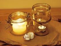 Candele nella fine di legno della cucina di concetto romantico bruciante di vetro di celebrazione su Immagini Stock