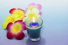 Candele profumate blu-chiaro e frangipane artificiale sulla pendenza immagini stock