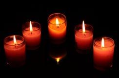 Candele rosse e rosa nell'oscurità la più densa trasparente delle tazze di vetro Fotografia Stock