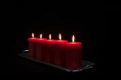 Candele rosse in una combustione di fila Fotografie Stock