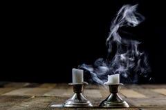 Candele saltate in candelieri d'argento con lo stoppino affumicato Fumo per Immagini Stock