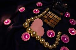Candele sentite, una tavolozza delle ombre, un cuore e belle perle su una coperta fotografia stock libera da diritti