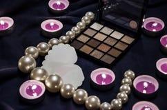 Candele sentite, una tavolozza delle ombre, un cuore e belle perle su una coperta fotografie stock