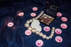 Candele sentite, una tavolozza delle ombre, un cuore e belle perle su una coperta immagini stock