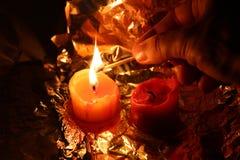 Candele su una stagnola per accendere le candele alla notte Fotografia Stock