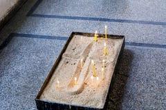 Candele in una sabbia in chiesa Fotografia Stock