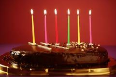 Candele variopinte dell'indicatore luminoso di compleanno in torta di cioccolato Immagini Stock Libere da Diritti