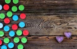 Candele variopinte di Tealight su fondo di legno Fotografia Stock