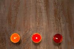 Candele variopinte sui bordi di legno immagine stock libera da diritti