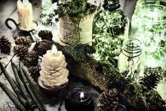 Candele verdi e nere, bottiglie luminose con le luci, muschio e succulente sulla tavola della strega Rituale gotico magico fotografia stock libera da diritti