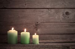 Candele verdi su fondo di legno scuro Immagine Stock
