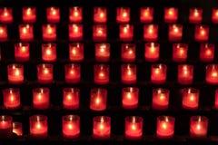 Candele in vetri rossi su uno scaffale Immagini Stock