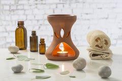 Candele votive di aromaterapia che bruciano in diffusore dell'olio essenziale per il trattamento di benessere in stazione termale Immagine Stock