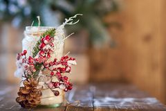 Candelero blanco adornado con el cono del pino y ashberry rojo en la tabla de madera Fotografía de archivo
