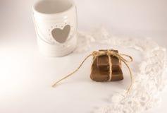 Candelero con el corazón, el cordón y el chocolateh en un backgrau blanco Foto de archivo libre de regalías