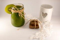 Candelero con el corazón, los smoothies, el cordón y el chocolate en un wh Imagenes de archivo