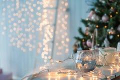Candelero con las luces de la Navidad y la luz atmosférica en fondo Fotografía de archivo
