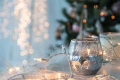 Candelero con las luces de la Navidad y la luz atmosférica en fondo Foto de archivo