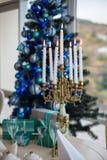 Candeliere con le candele accese ad un albero di Natale con i regali fotografia stock