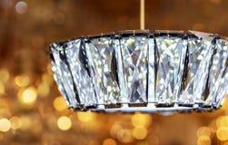 Candeliere a cristallo moderno con la sospensione sul fondo del bokeh immagine stock libera da diritti