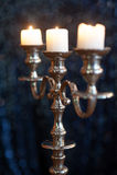 Candeliere d'argento con tre candele bianche brucianti su fondo scuro Fotografia Stock