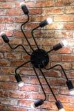 Candeliere della parete sotto forma di ragno su un muro di mattoni Stile del sottotetto fotografia stock