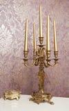 Candeliere dorato con cinque candele sulla tavola bianca Fotografie Stock
