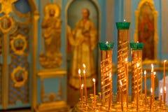 Candeliere rotondo con le candele brucianti sui precedenti dell'altare in Christian Church immagini stock