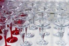 Candelieri di vetro trasparenti e con una gamba rossa sulla finestra del negozio immagini stock libere da diritti