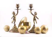 Candelieri dipinti dorati con l'immagine di un ragazzo e gli elementi floreali, le mele, le arance, un vetro e un disco su un fon Fotografia Stock Libera da Diritti