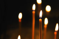 Candels, fire in the dark. Good quality picture of long thin church candles, burning in the darkness, some candles are in focus, some are blurred at the Royalty Free Stock Photography