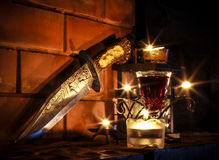 Candels light and dagger on fireplace Stock Photo