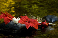 Candels sitting on rock with christmas decorations Royalty Free Stock Image