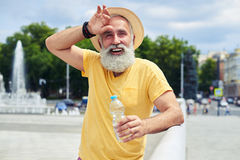 Candid bearded man standing with plastic bottle. Close-up shot of exhausted bearded man standing with plastic bottle. Wearing bright clothes and straw hat Stock Image