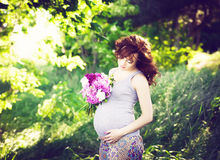 Candid carefree adorable pregnant woman in field with flowers at Stock Images