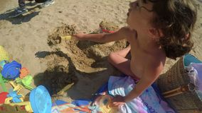 A candid child is playing on the beach with bucket and spade 2 FDV. A funny candid child is playing on the beach with bucket and spade stock video
