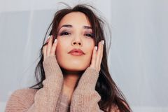 Candid close up portrait of sensual smiling asian girl young woman with dark long hair in cozy beige sweater. The Candid close up portrait of sensual smiling royalty free stock images