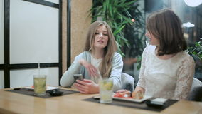 Candid conversation between girls in restaurant. Candid conversation between two girls in restaurant, Two girls gossiping in a Japanese restaurant. Girlfriends stock video footage