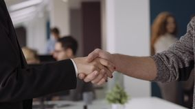 Candid creative busines man and woman in office habdshaking hands and discussing succesefull project. Close up hands. Candid creative busines man and woman in stock video footage