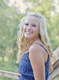 A beautiful blonde high school senior. A female senior portrait shoot smiles at the camera during a summer shoot in Iowa stock image