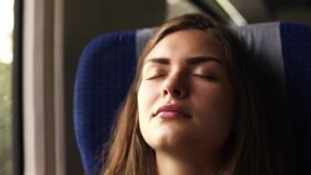 A candid female traveling by train and falls asleep when the landscape passes. Beautiful young brunette. Face close up.  stock video
