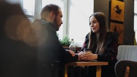 Candid image of young couple in a coffee shop. Caucasian man and woman sitting with a dog in a cafe. Long shot of loft. Style coffee shops. Couple holding hands stock footage