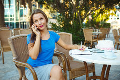 Candid image of a young woman talking on the phone and makes not Royalty Free Stock Photos