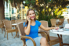 Candid image of a young woman talking on the phone and makes not Stock Photos