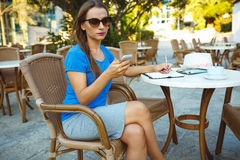 Candid image of a young woman using smartphone and makes notes i Royalty Free Stock Images